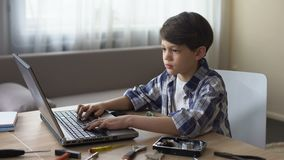 Bambino in età prescolare maschio astuto che cerca le istruzioni sul computer portatile, hobby del disco rigido dell'IT archivi video