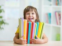 Bambino in età prescolare sveglio della ragazza del bambino con i libri dell'interno Immagine Stock