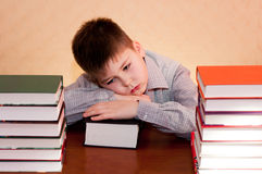 Bambino faticoso con la pila di libri Fotografia Stock