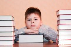 Bambino faticoso con la pila di libri Fotografia Stock Libera da Diritti
