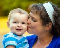 Bambino felice baciato dalla mamma Immagini Stock