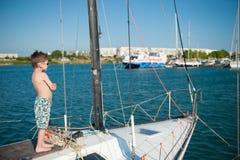 Bambino felice a bordo dell'yacht di lusso in porto marittimo nel giorno di estate Fotografie Stock