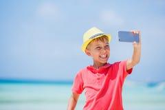 Bambino felice in cappello giallo che fa selfie e che si diverte alla spiaggia tropicale Concetto di vacanze estive Fotografia Stock