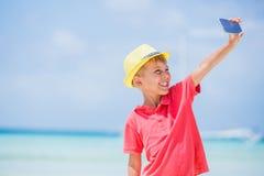 Bambino felice in cappello giallo che fa selfie e che si diverte alla spiaggia tropicale Concetto di vacanze estive Immagini Stock Libere da Diritti