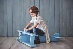 Bambino felice in cappello pilota che gioca con l'aeroplano di legno contro l'infanzia Fantasia, immaginazione festa fotografie stock libere da diritti