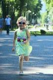Bambino felice che corre nel parco della città Bambina che gode del funzionamento immagini stock