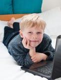 Bambino felice che esamina il suo computer portatile Immagini Stock
