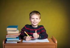 Bambino felice che fa compito con il pollice su, libri sulla tavola fotografia stock libera da diritti