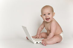 Bambino felice che gioca con il mini computer portatile Immagine Stock Libera da Diritti