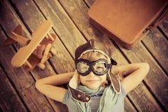 Bambino felice che gioca con l'aeroplano del giocattolo
