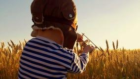 Bambino felice che gioca con l'aeroplano del giocattolo sul giacimento di grano sul fondo di tramonto Il ragazzo mostra il volo d archivi video