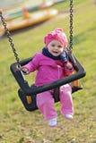 Bambino felice che gioca con l'oscillazione Immagini Stock
