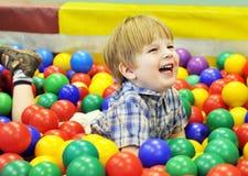 Bambino felice che gioca con le palle colorate Immagine Stock