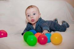 Bambino felice che gioca e che si diverte con le palle variopinte Immagini Stock