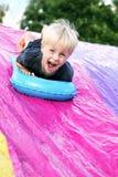 Bambino felice che gioca fuori sullo Slittamento-n-scorrevole del cortile fotografie stock