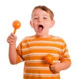 Bambino felice che gioca i maracas e sign Fotografia Stock