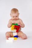 Bambino felice che gioca nel costruttore che si siede sul pavimento Immagini Stock