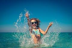 Bambino felice che gioca nel mare Immagine Stock