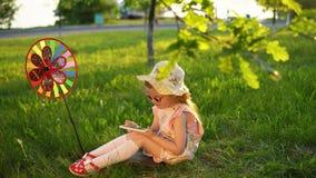 Bambino felice che gioca sull'erba sotto le giovani querce in un parco pubblico al tramonto video d archivio