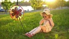 Bambino felice che gioca sull'erba sotto le giovani querce in un parco pubblico al tramonto stock footage