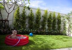 Bambino felice che gioca in un raggruppamento Fotografia Stock