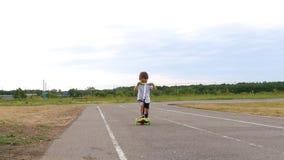 Bambino felice che guida un motorino sulla pista al rallentatore stock footage