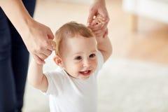 Bambino felice che impara camminare con aiuto della madre fotografie stock