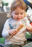 Bambino felice che mangia cono gelato con il cucchiaio Fotografia Stock