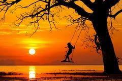 Bambino felice che oscilla al bello tramonto su un'isola tropicale Immagini Stock