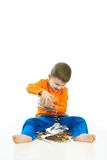 Bambino felice che rovescia i dolci sulla seduta del pavimento Fotografie Stock