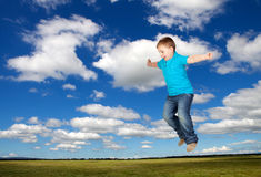 Bambino felice che salta sul prato Fotografia Stock