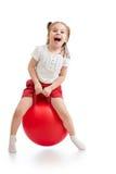 Bambino felice che salta sulla palla di rimbalzo immagine stock