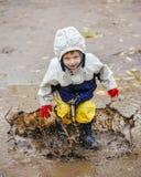 Bambino felice che salta sulle pozze in stivali di gomma Immagini Stock