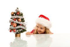 Bambino felice che si apposta intorno ad un piccolo albero di Natale Fotografie Stock Libere da Diritti