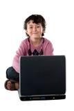 Bambino felice che si siede con un computer portatile Fotografie Stock