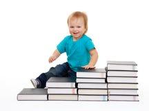 Bambino felice che si siede sui punti dei libri Immagini Stock Libere da Diritti