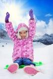 Bambino felice che si siede sulla slitta il giorno soleggiato immagini stock libere da diritti