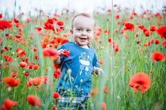 bambino felice che sorride in un campo dei papaveri fotografia stock