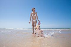 Bambino felice che spruzza alla spiaggia Immagine Stock