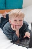 Bambino felice che studia e che utilizza il suo computer portatile nella sua camera da letto Immagine Stock Libera da Diritti