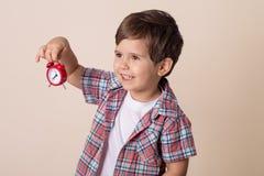 Bambino felice che tiene orologio rosso su fondo grigio Bambino con la sveglia immagini stock libere da diritti