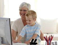Bambino felice che usando un labtop con la sua nonna fotografie stock libere da diritti
