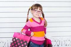 Bambino felice con i sacchetti della spesa. Sta godendo dei regali e delle feste Immagini Stock
