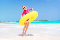 Bambino felice con il cerchio di gomma gonfiabile divertendosi sulla spiaggia bianca Fotografia Stock