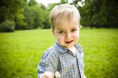 Bambino felice con il fiore Immagine Stock