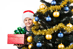 Bambino felice con il regalo vicino all'albero di Natale Fotografie Stock Libere da Diritti