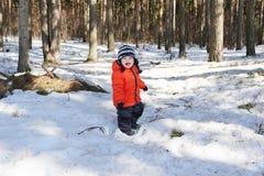 Bambino felice contro gli alberi in foresta Fotografia Stock