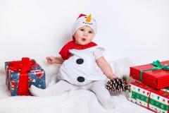 Bambino felice in costume del pupazzo di neve con i contenitori di regalo del regalo di Natale Immagini Stock Libere da Diritti