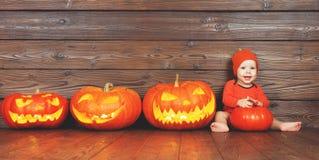 Bambino felice in costume per Halloween con le zucche sulla parte posteriore di legno Fotografie Stock