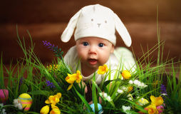 Bambino felice del bambino vestito come il coniglio di coniglietto di pasqua sull'erba Immagine Stock